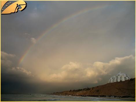 "A Rainbow colloring dark skys... High above ""Holliday inn"" Hotel. Ashqelon Feb 08"
