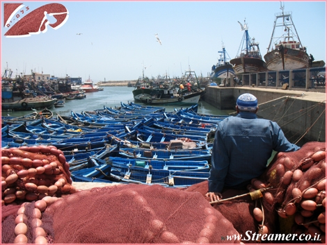 The true collors of Morocco... A fishermman sits and watch an ocean of boats... - Essauira Port, The Atlantic ocean Morocco. June 08.