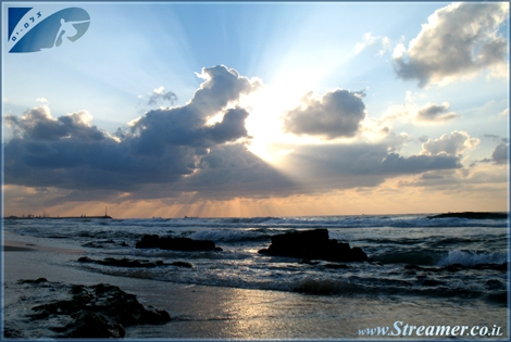 The sun is hiding behind the clouds, It's rays are colloring the sky - Coast of Israel Nov. 08