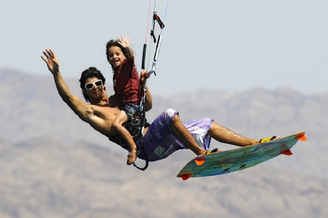 "<div align=""center""><strong>Eli Zarka kitesurfing while carrying a boy on his shoulders...! Click on photo to watch the full album of the nomber one kitesurfer from Ashqelon</strong><br /></div>"
