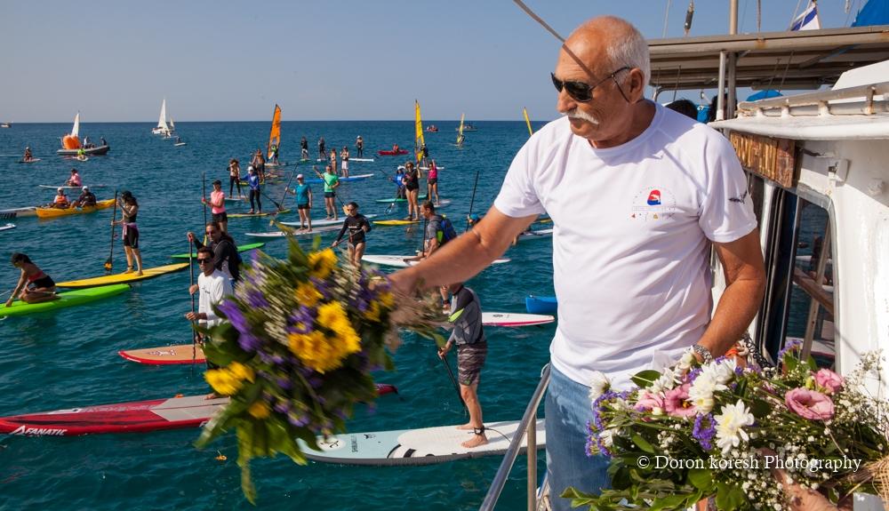 """זוכרים וממשיכים את המורשת. המשט ה-18 לזכר סא""""ל יוסי קורקין שנפל בפעולת השייטת בלבנון בשנת 1997. אריה קורקין שולח זר פרחים אל הים לזכר בנו."""