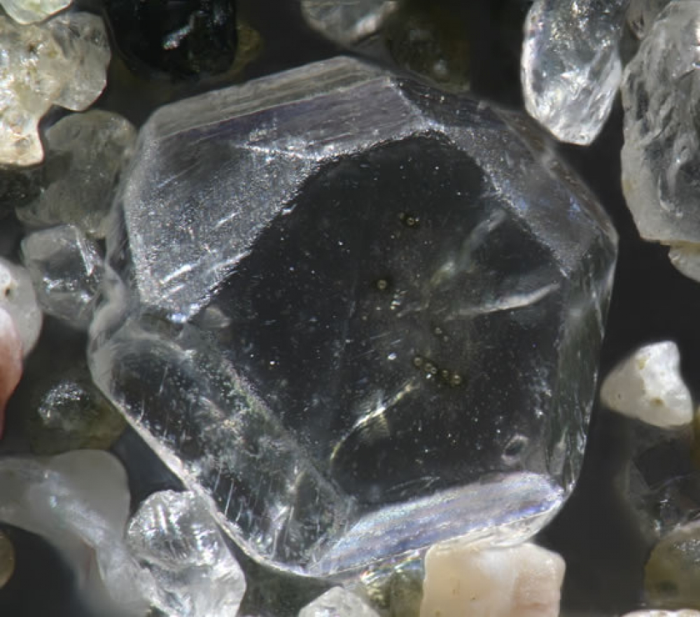 מרבית גרגרי החול הם קריסטלים זעירים ומבריקים. בתמונה: גרגר חול מחוף מיפן שמכיל מה שנראה כמו קריסטל ספיר.
